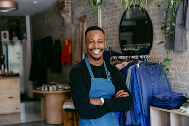 a man in denim apron smiles for the camera