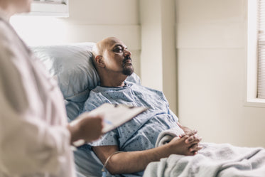 a man lies in a hospital bed as a doctor reads his chart