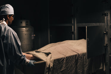 a man pushes a body on a tray into the freezer in the morgue