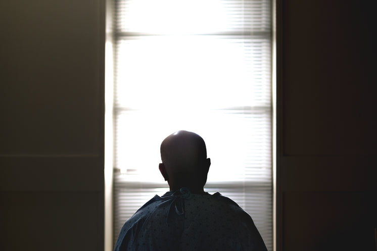 A Man Sat On A Hospital Bed Silhouetted Against The Window