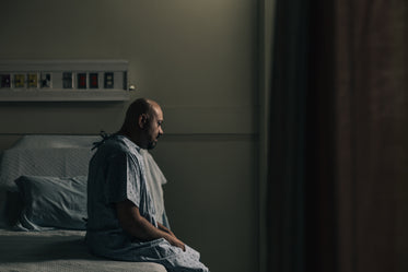 a man sits on his hospital bed and stares at the ground