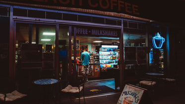 a man stands at the counter of a coffee shop