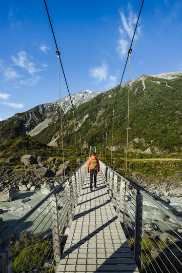 a man walking across a suspension bridge