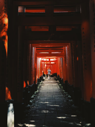 a man wanders through red arches in japan
