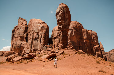 a man with a camera stands small against red desert pillars