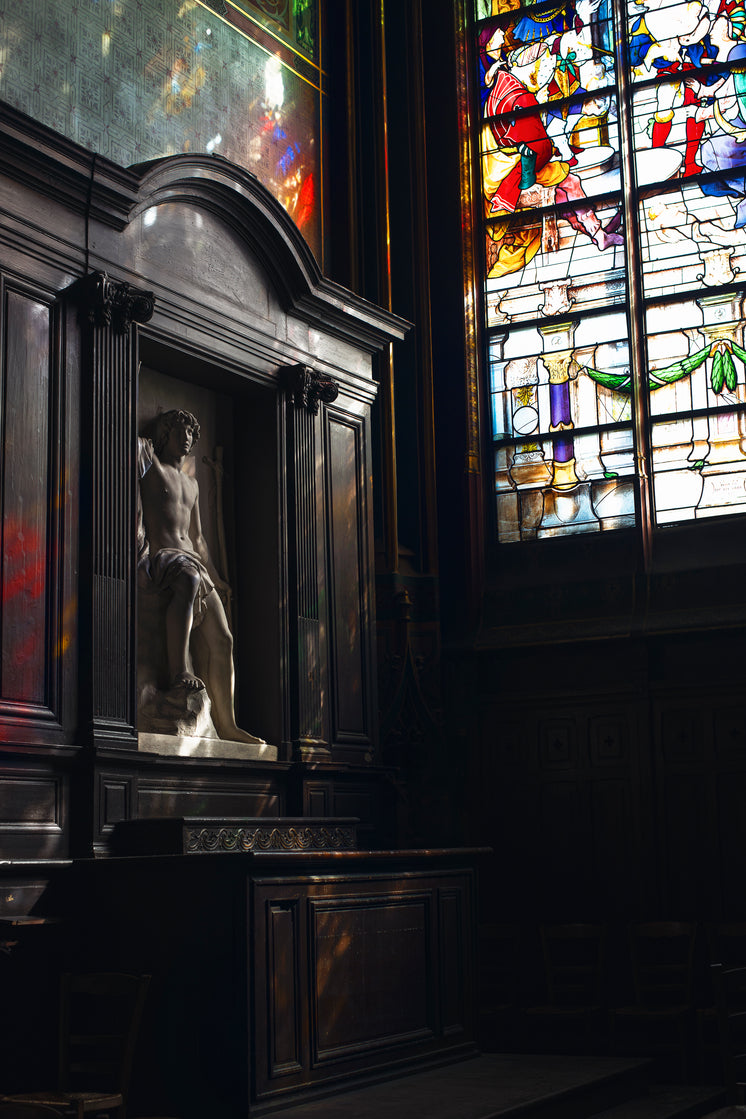 A Marble Statue Of A Man In A Little Wooden Niche