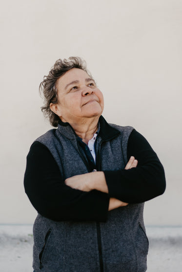 a mature woman crosses arms reflectively