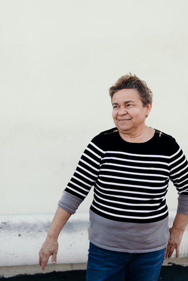 a mature woman in a sweater smiling