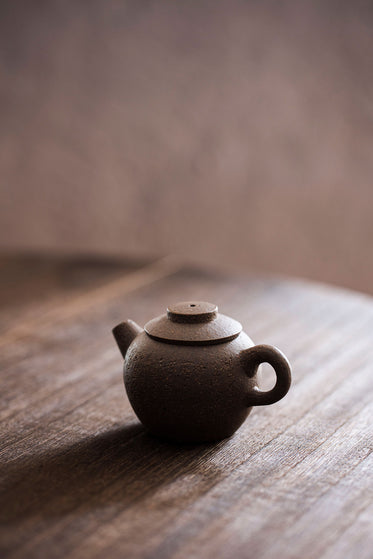 a mini brown teapot with carved characters on a wooden tabletop