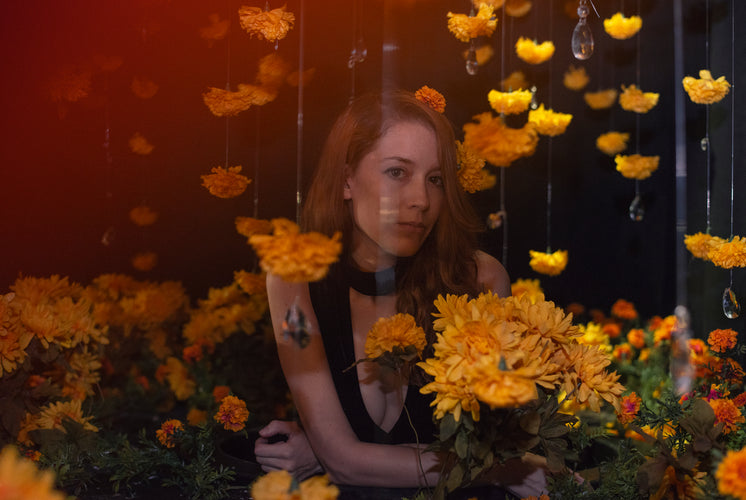 A Model Gazes Out At You From Beyond The Veil Of Flowers