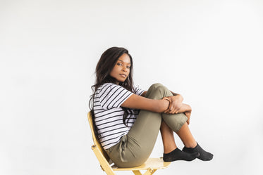 a model holds knee to chest on chair pensively