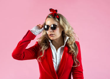 a model in red suit jacket removing sunglasses