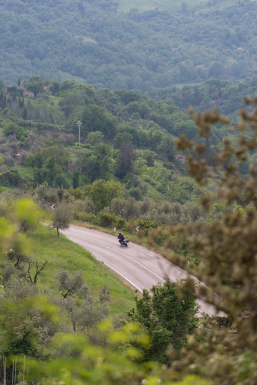 a motorcycle takes a curve on a highway around a hill