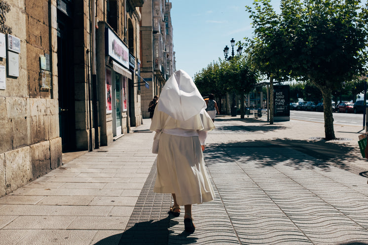 A Nun In A White Habit Strolls A Sunny Pedestrian Walk