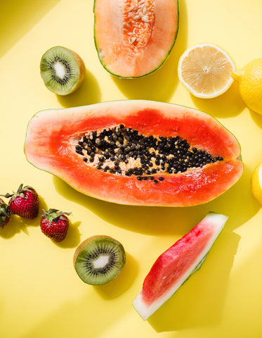 a papaya is surrounded by fruit on yellow background