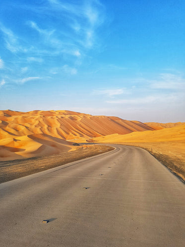 a paved road turns into tall sand dunes