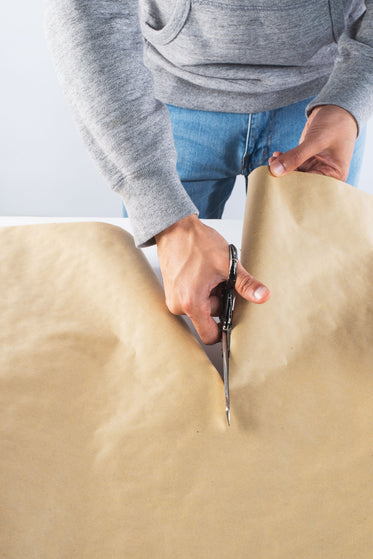 a person carefully cuts through kraft paper