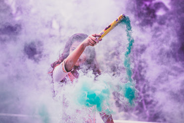 a person surrounded by purple and blue smoke