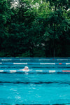 a person swimming lanes in outdoor pool by tall trees
