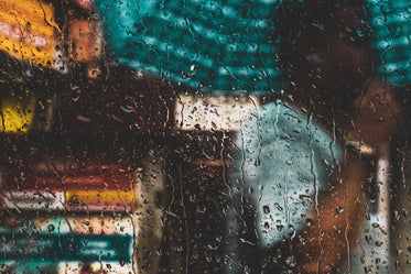 a person with an umbrella through a rain-speckled window