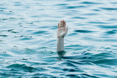 a persons hand reaches out toward the blue water