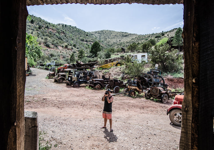 A Photographer In A Desert Graveyard Of Cars Snaps A Photo
