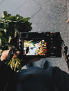 a picture of a produce stall through a camera screen