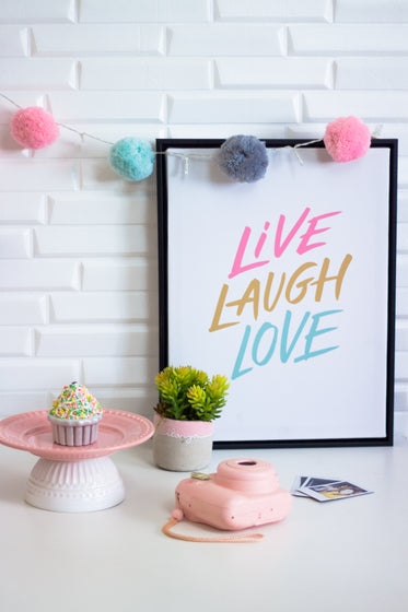 "a picture reads ""live laugh love"" joined by random objects"