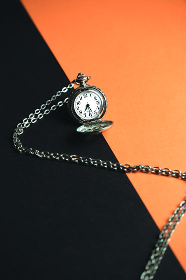 a pocket watch laying on a black and orange background