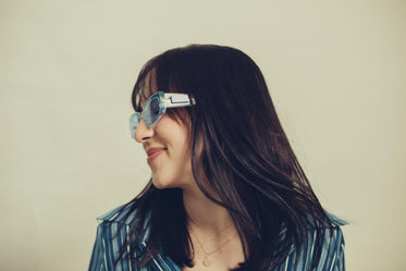 a profile of a woman in blue tinted sunglasses