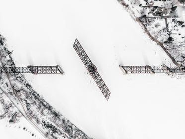 a railway swing bridge on a frozen river covered in snow