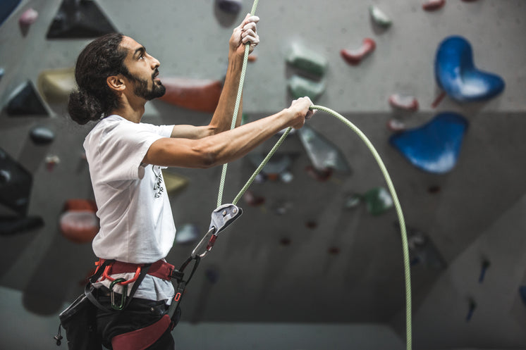 A Rock Climber Belaying A Climbing Rope