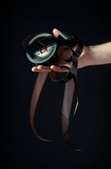 a roll of film reel curls out of a hand