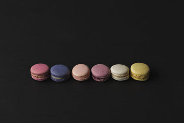 a row of colored macarons in shadows