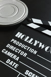 a silver film reel canister and a movie clapper board