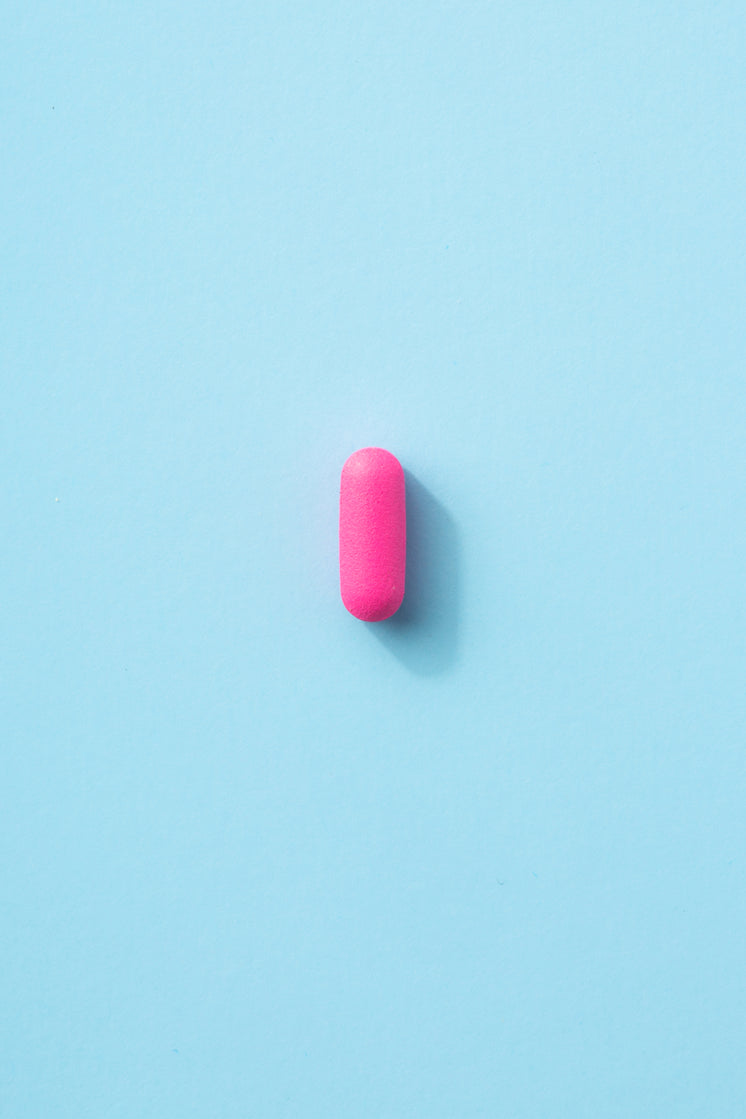 A Single Pink Pill On A Baby Blue Surface