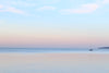 a single sailboat in still waters