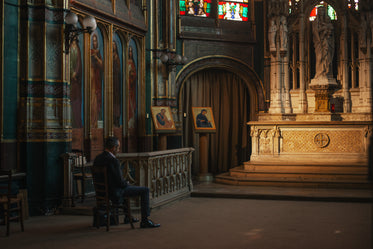 a solitary man in a suit sits on a chair in a baroque church