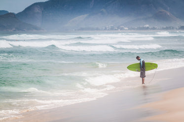 a surfer contemplates the water's edge