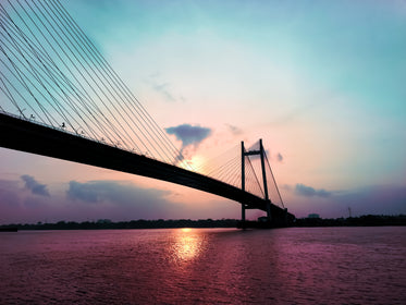 a suspension bridge silhouetted by sunset