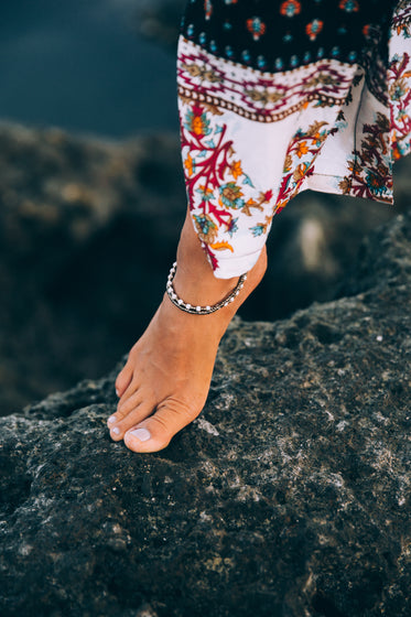 a tanned woman exhibits anklet on rocky seashore