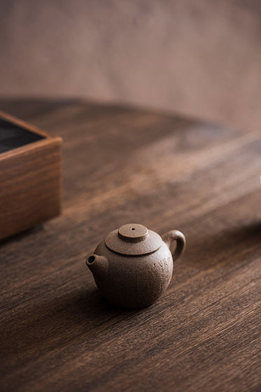 a tiny carved teapot sits on a wooden table