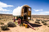 a traditional caravan rests under blue skies in the plains