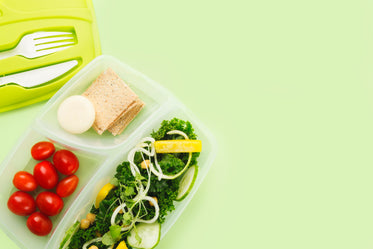 a tupperware lunch box separates salad ingredients