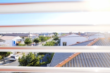 a view of rooftops through window blinds