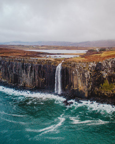a waterfall cascades down the side of a large cliff