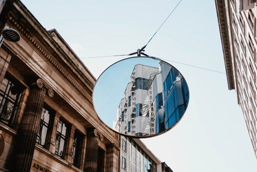a white building is reflected in a large traffic mirror