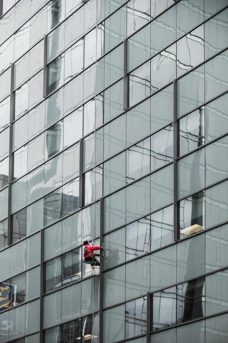 A Window Washer Dangles From A Skyscraper