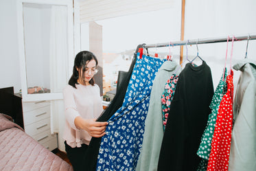 a woman holding a dress browses her bedroom clothing rack