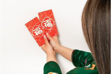 a woman holds two red envelopes